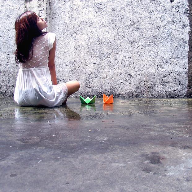 دختری که روی زمین کنار دو قایق کاغذی نشسته است